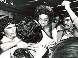 Dinamite é abraçado por Dulce Rosalina no aeroporto em seu retorno ao Rio